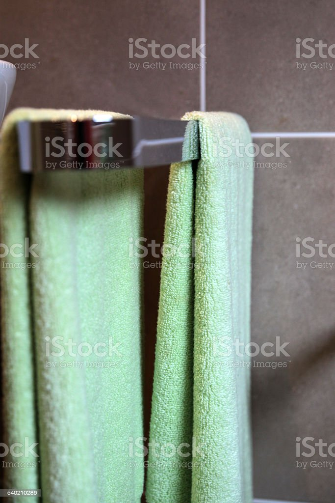 Towelrail with green terry cloth towels stock photo