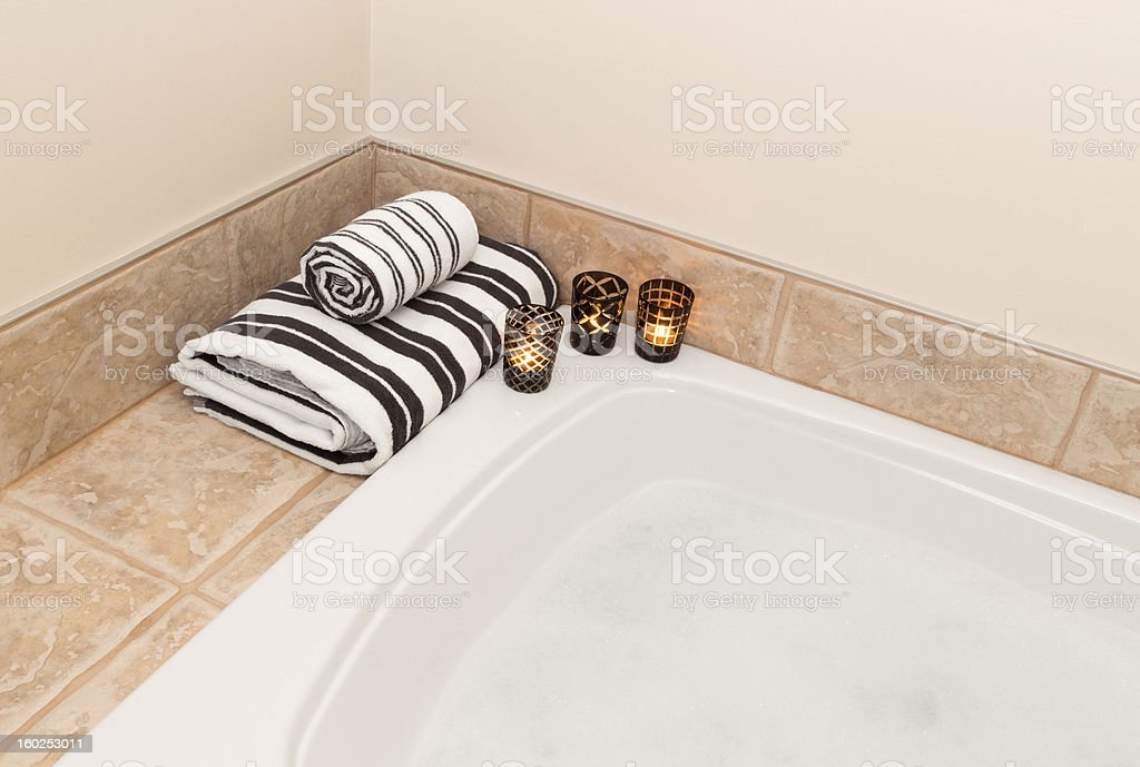Towels, candle lights and bath with foam royalty-free stock photo