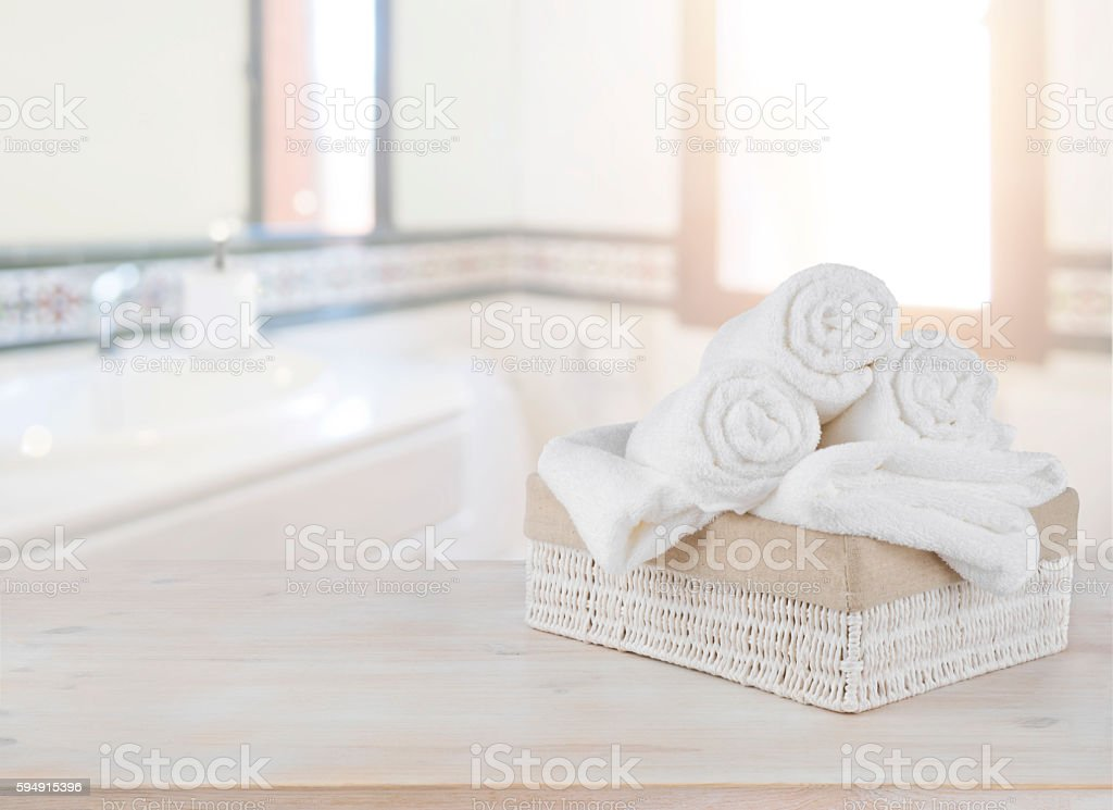 Towels in basket on wooden table over defocused bathroom background stock photo