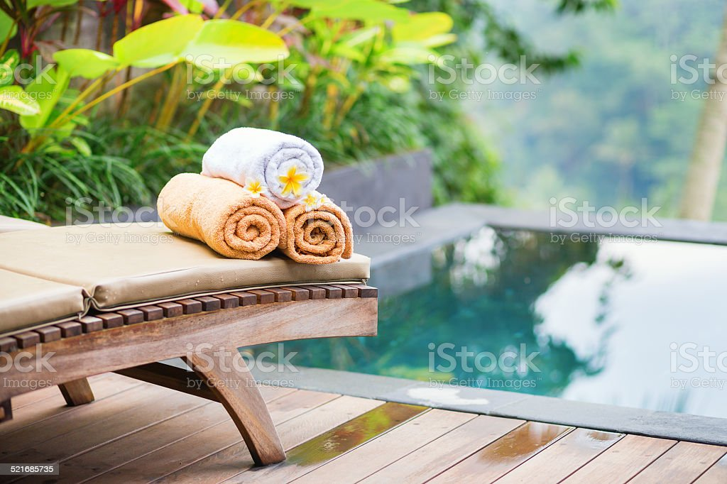 Towels with white frangipani flowers in spa stock photo