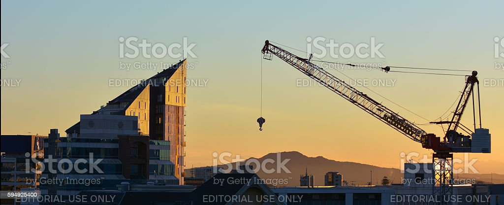 Tower crane against Auckland skyline at sunrise stock photo