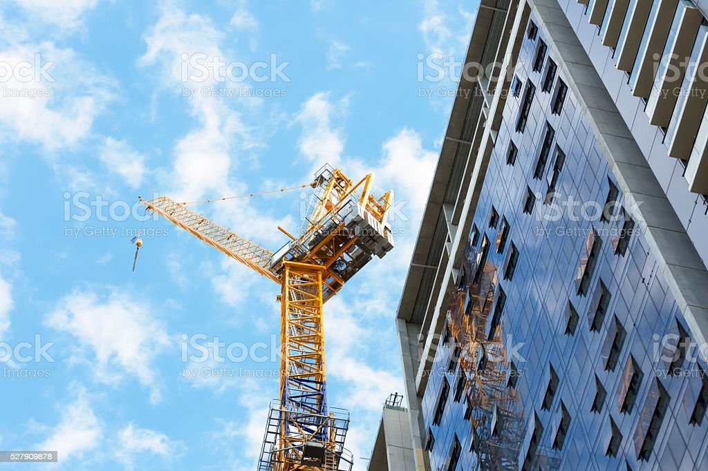 Tower crane at construction site of skyscraper, copy space stock photo
