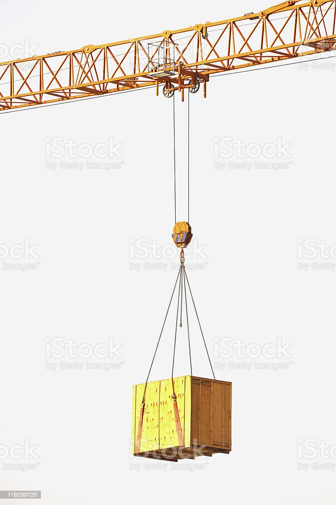 A tower crane carrying a wooden box stock photo