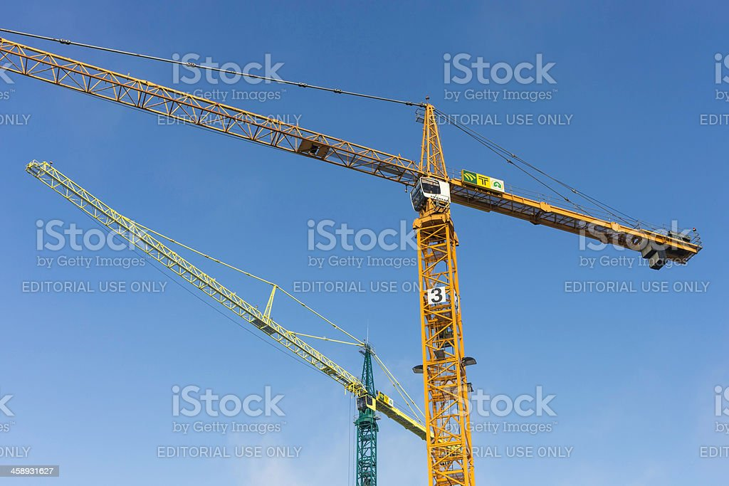 Tower cranes against a blue sky stock photo
