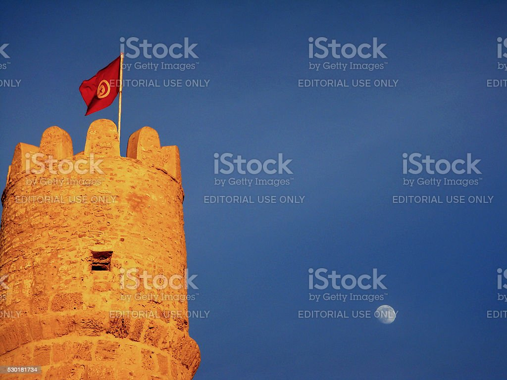 Tower of Ribat in Monastir and Tunisian Flag royalty-free stock photo