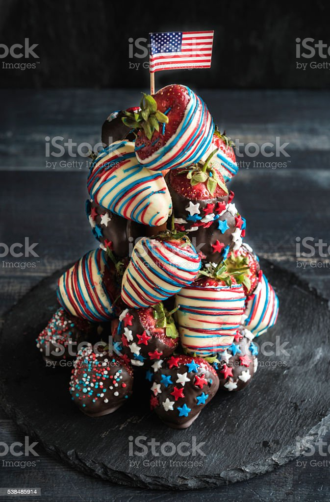 Tower of strawberries in chocolate with USA flag decoration on wooden...