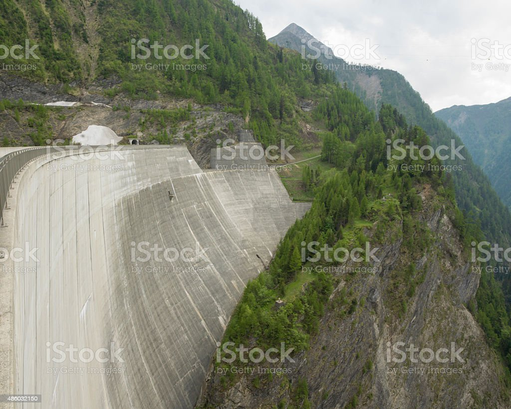 Towering concrete dam in mountain setting stock photo