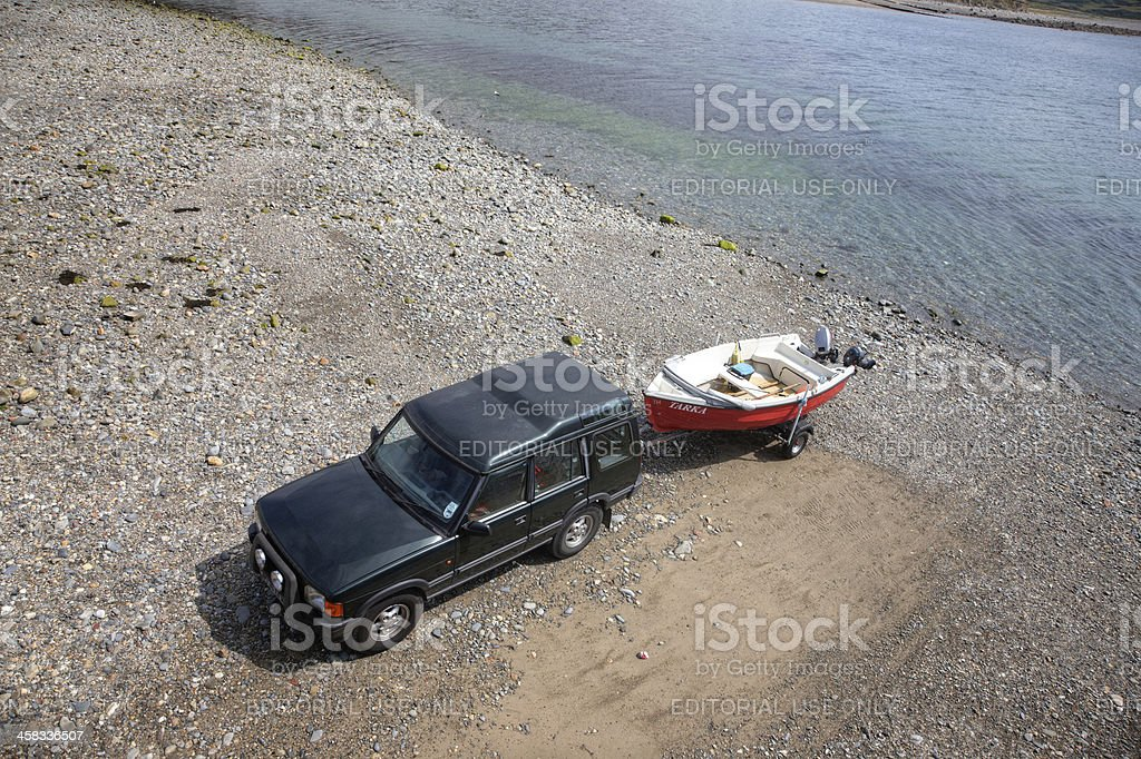 SUV towing small boat on beach stock photo