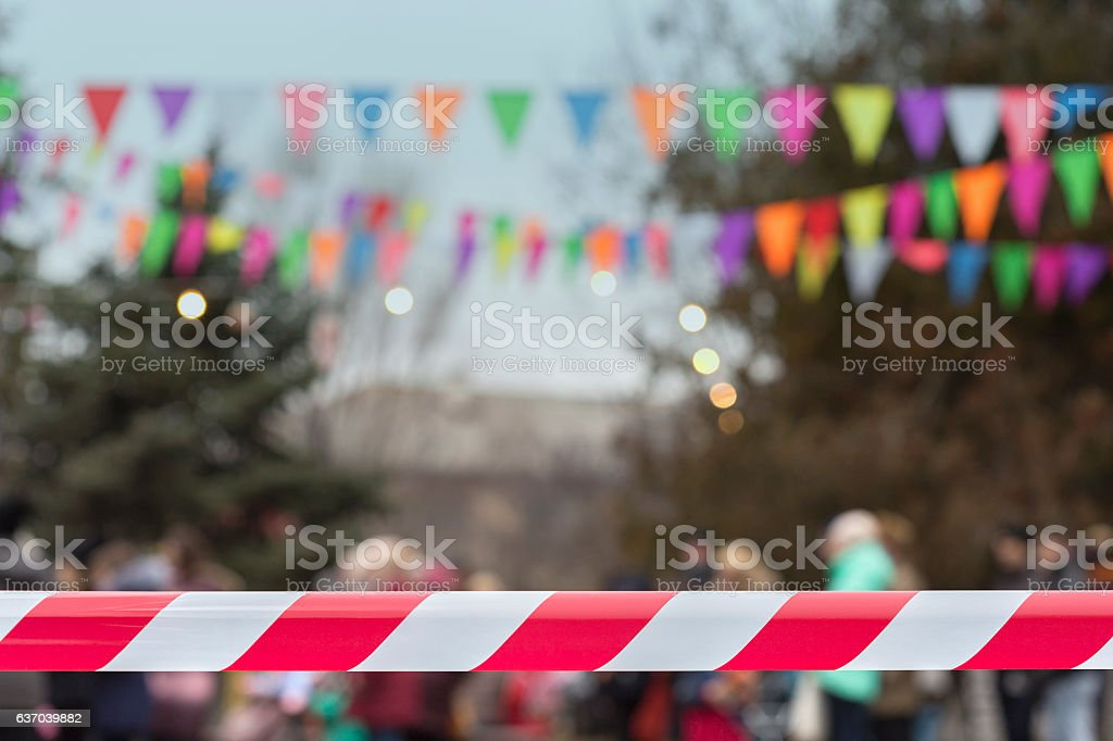 Town celebration Defocused crowd behind red cordon tape stock photo