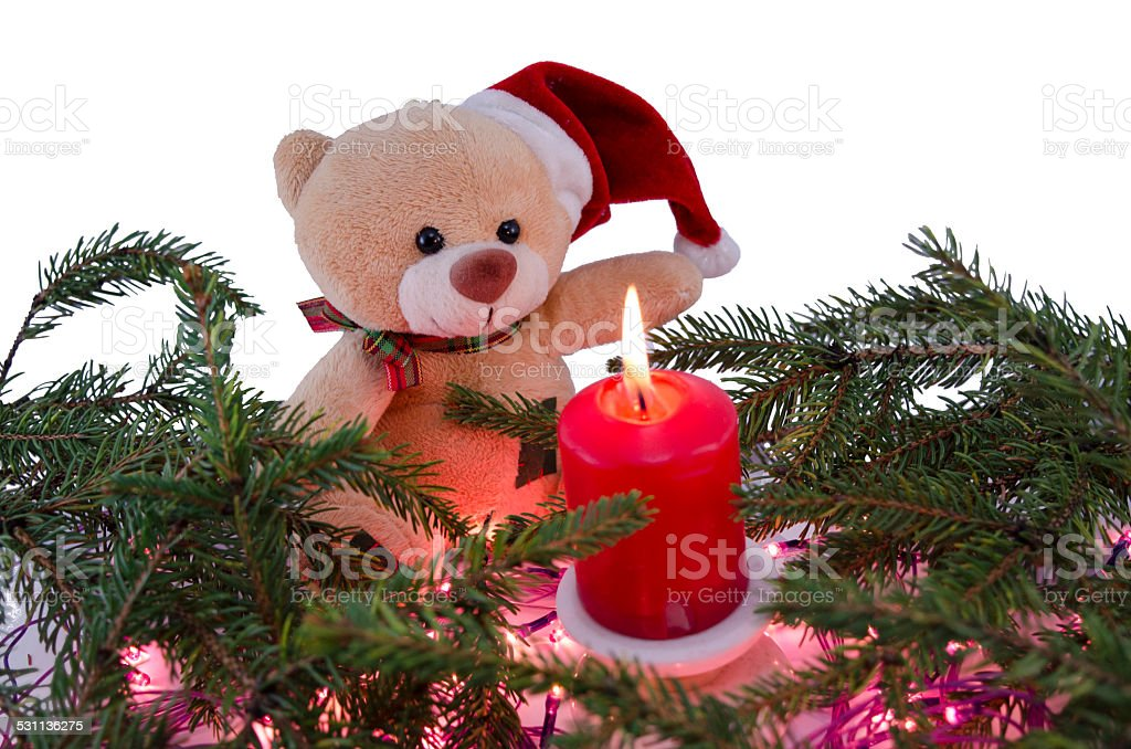 Toy bear and a red Christmas candle royalty-free stock photo