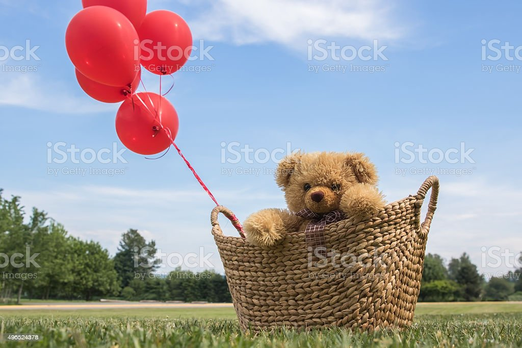 Toy Bear in a Basket with Red Balloons stock photo