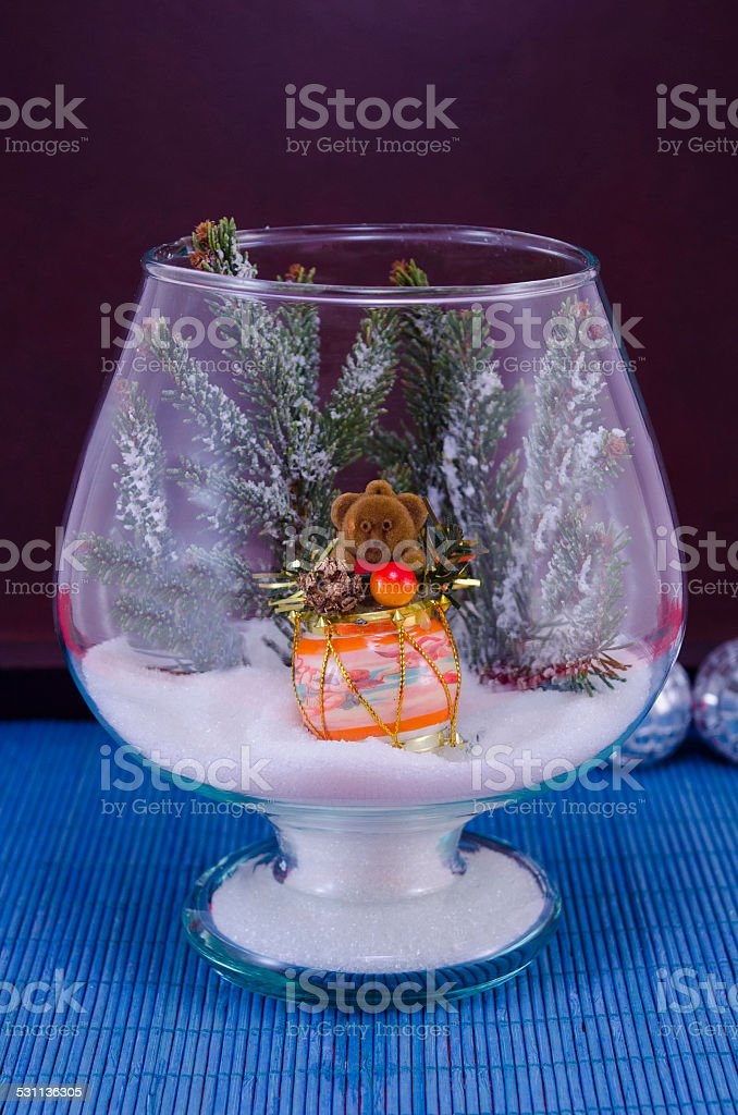 Toy bear in a glass vase covered with snow royalty-free stock photo