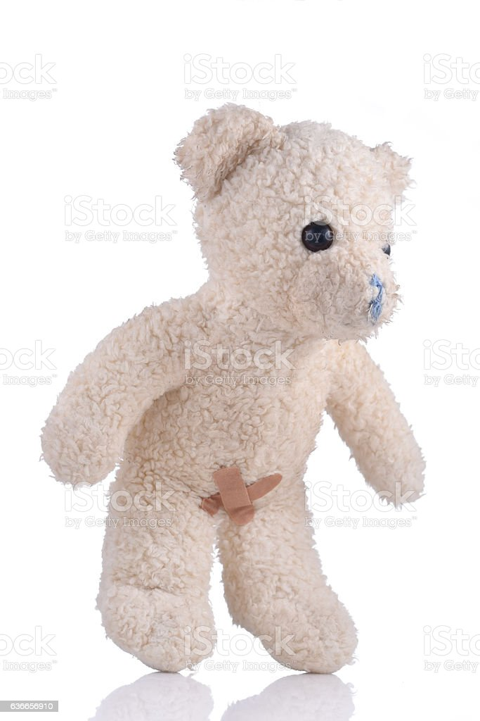 Toy bear with adhesive bandages on his private parts 3/4 stock photo