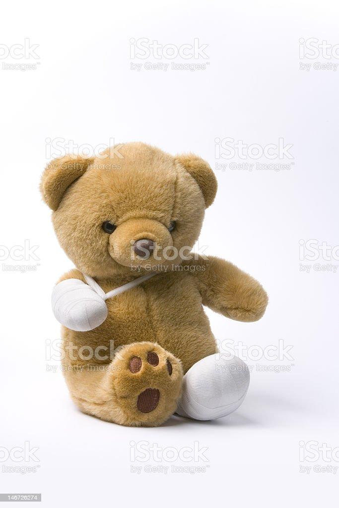 Toy bear with broken legs stock photo