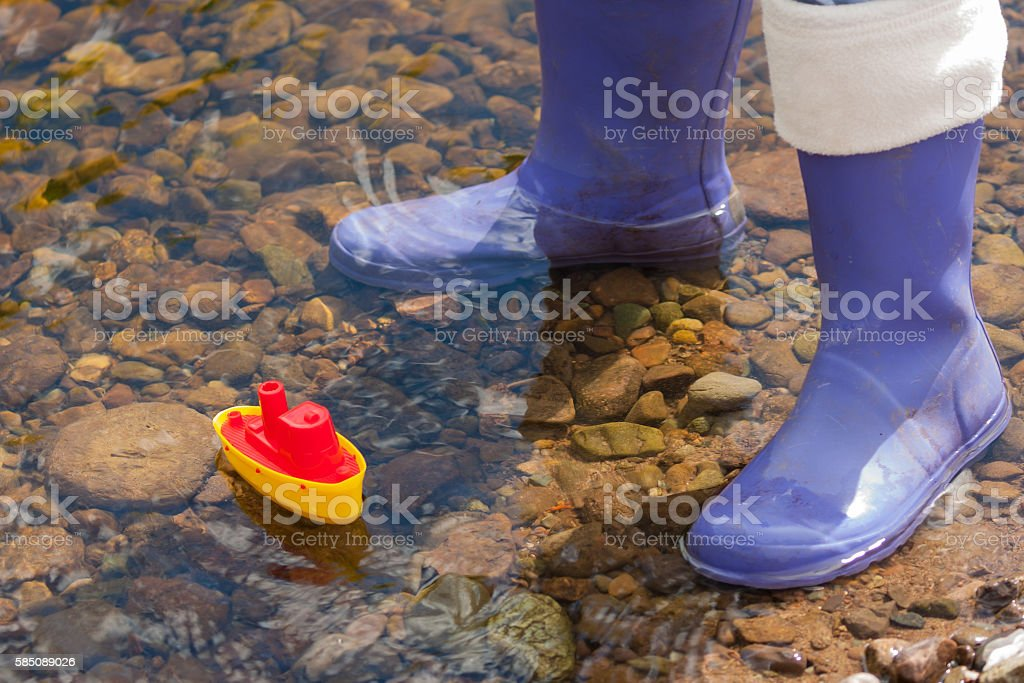 toy boat and kids wellies stock photo