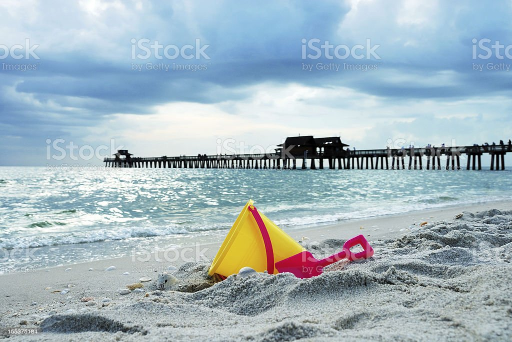 Toy bucket on beach with pier in background stock photo