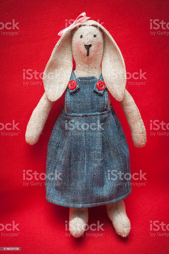 toy bunny stands. On red background. stock photo