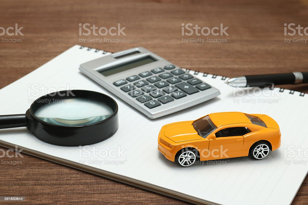 Toy car, magnifying glass, calculator, pen and notebook. stock photo