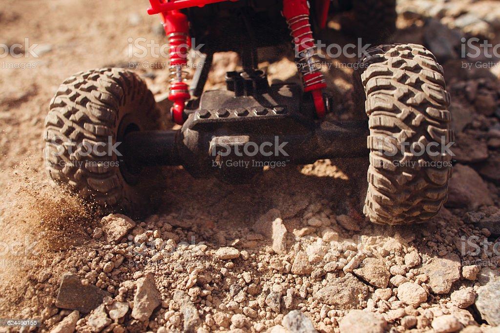 Toy car skidding on dry landscape, close-up stock photo