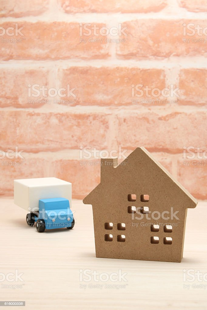 Toy car truck and house in front of brick wall. stock photo