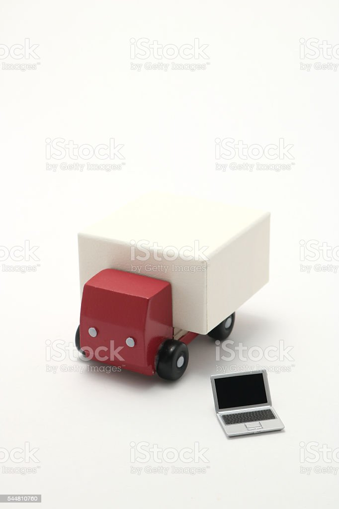 Toy car truck and miniature laptop on white background. stock photo