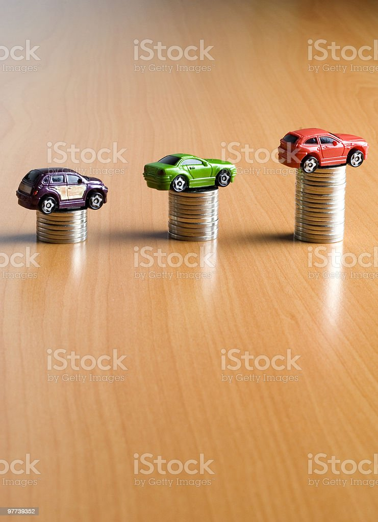 Toy cars on stacked coins royalty-free stock photo