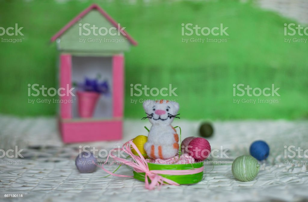 Felt a toy cat in a basket with balls. In the background is a...