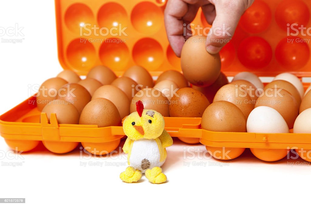 Toy chicken sits in front of orange container with eggs stock photo