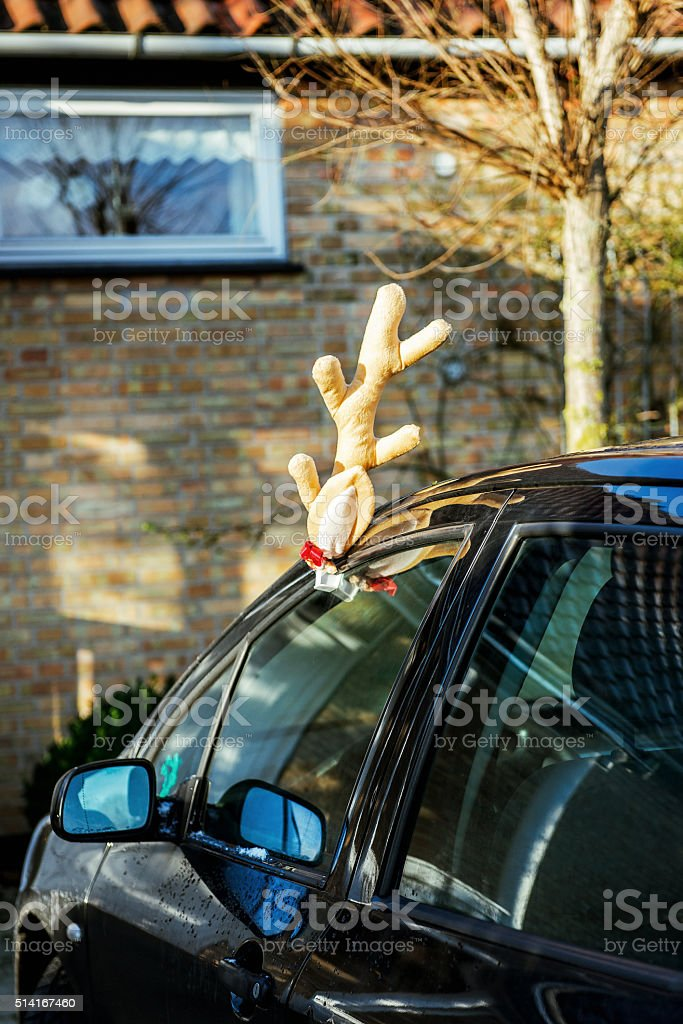 Toy deer antlers on a parked car stock photo