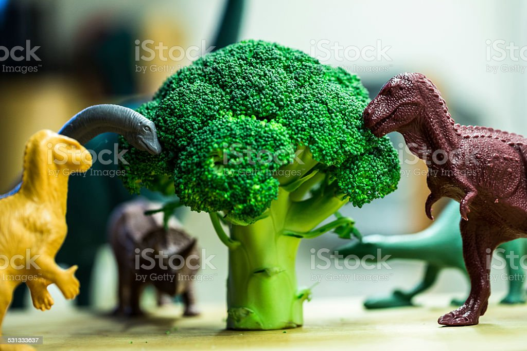 Toy dinosaurs with broccoli stock photo
