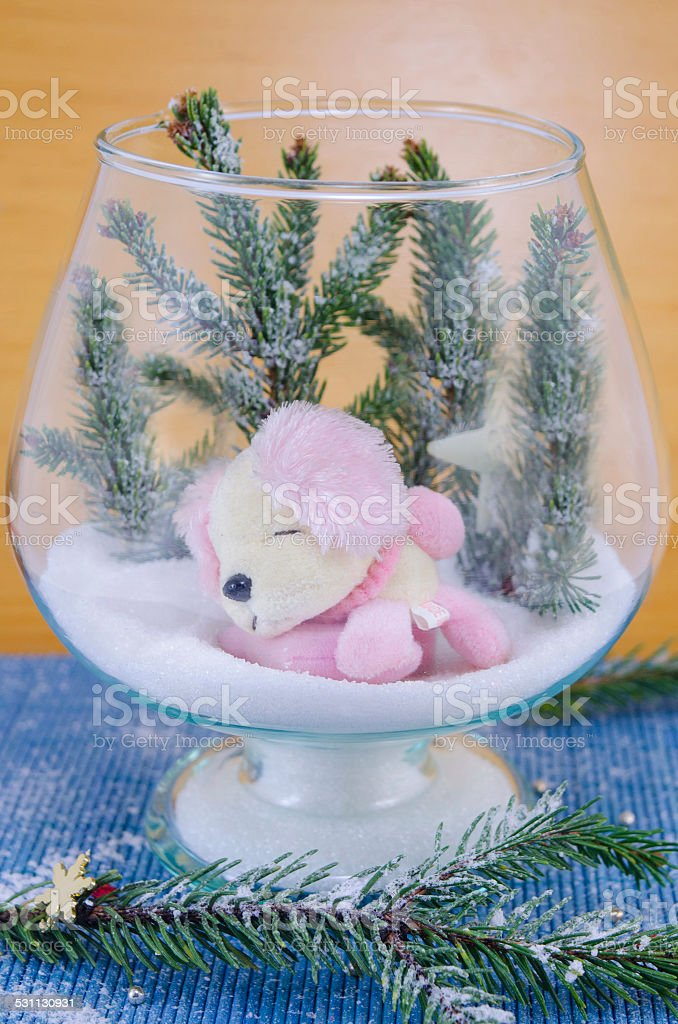Toy dog sleeping on snow in a glass bowl royalty-free stock photo
