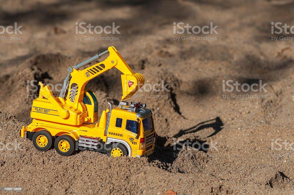 Toy excavator in the sand stock photo