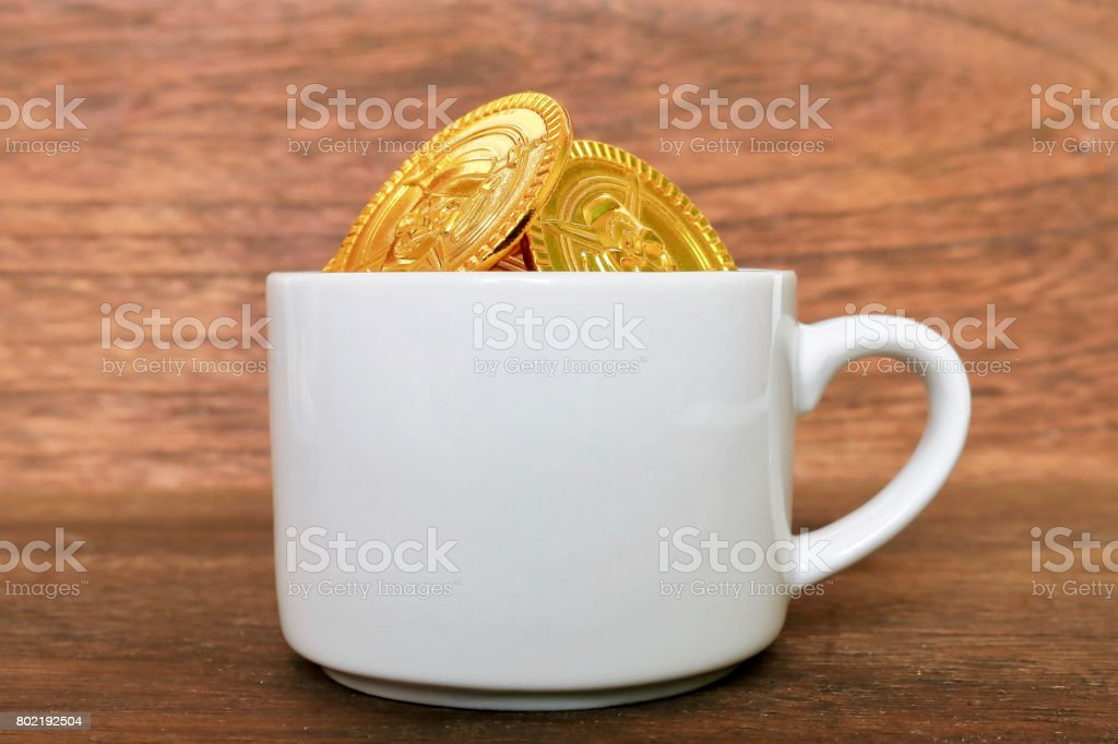 Toy gold coins and cup stock photo