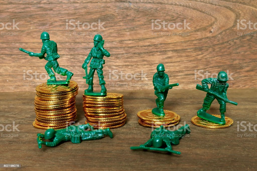Toy gold coins and soldier stock photo