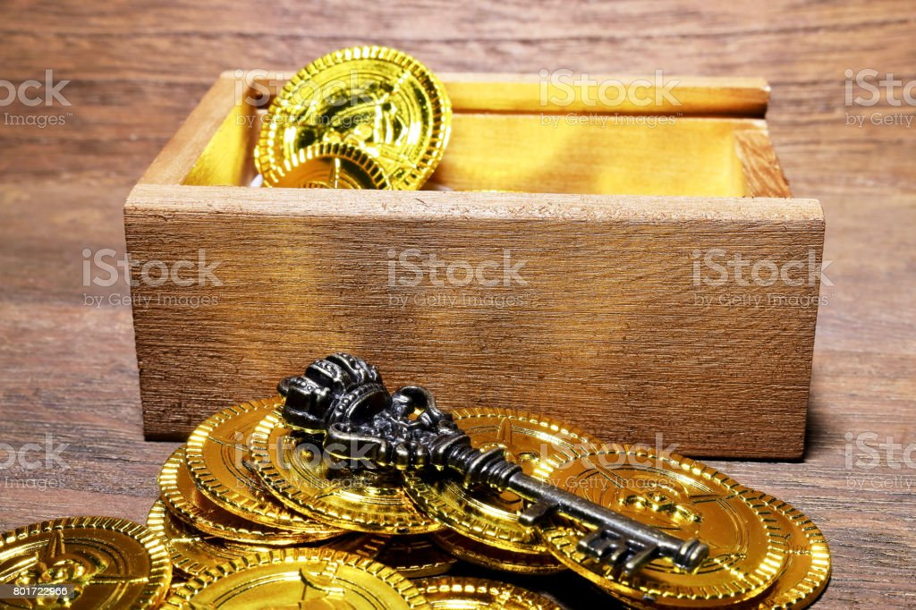 Toy gold coins and wood box stock photo