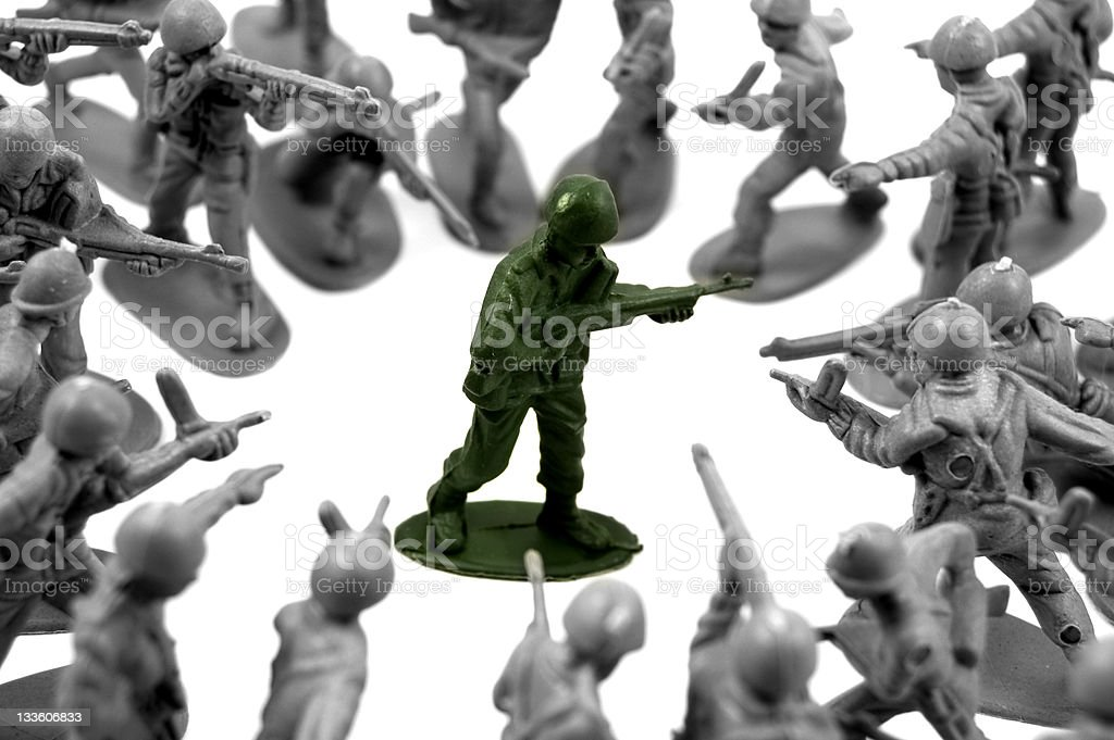toy green army man surrounded stock photo