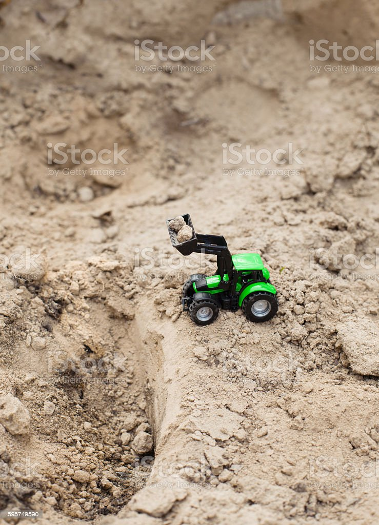 toy green tractor on sand career,  equipment stock photo