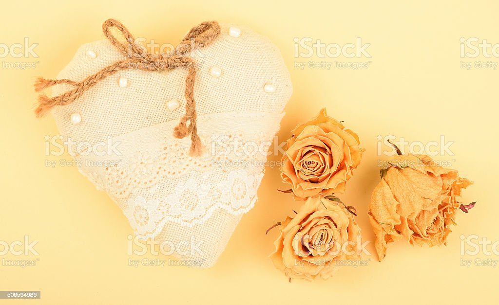 Toy heart and dried roses on beige paper royalty-free stock photo