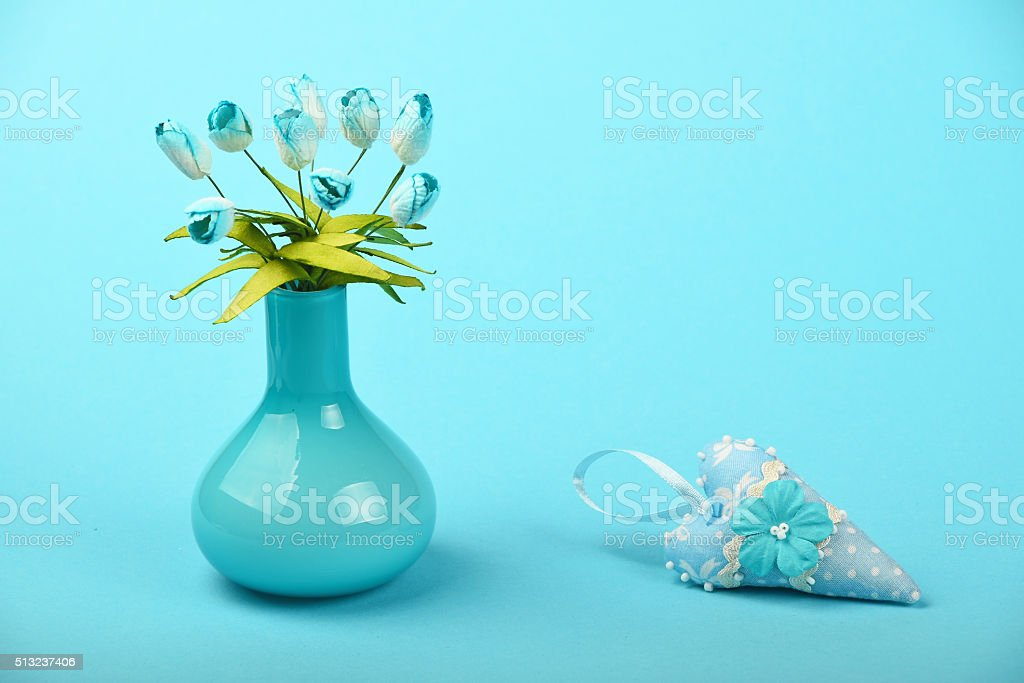 Toy heart and vase with silk tulips on blue background royalty-free stock photo