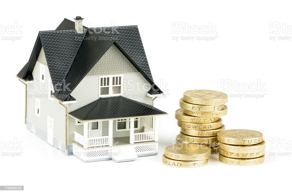 Toy home is next to pile of gold showing rising house prices royalty-free stock photo