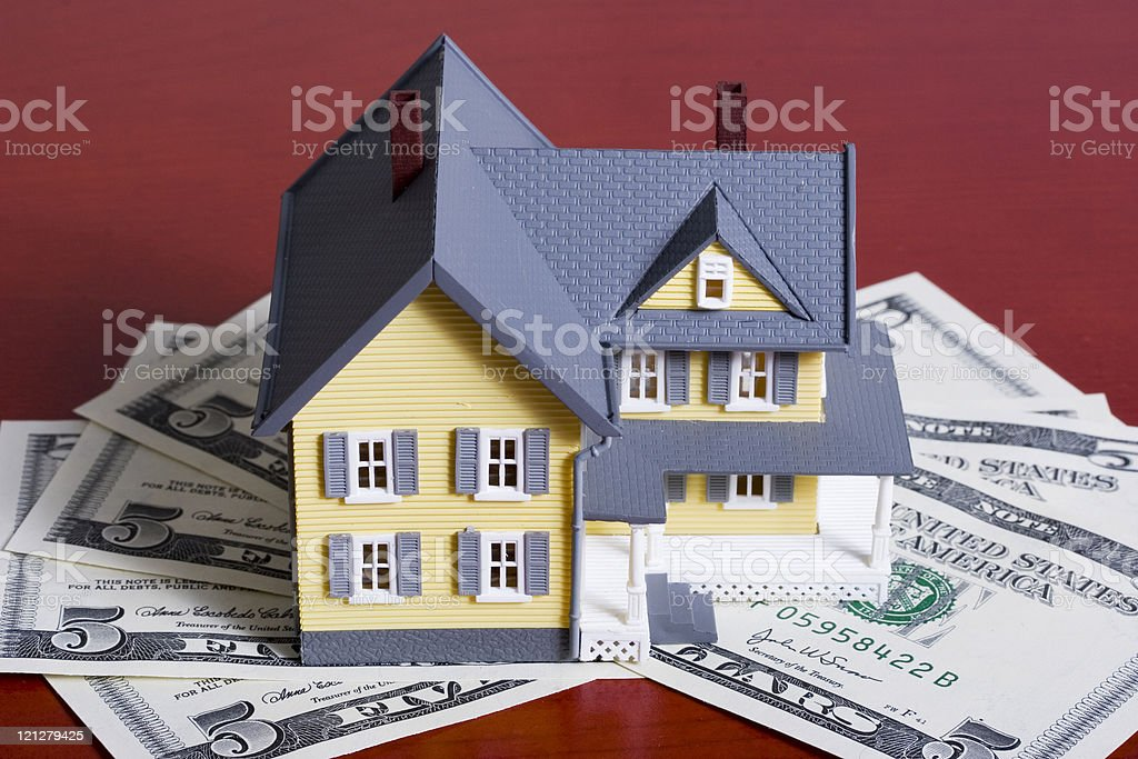 Toy home on dollar bills representing home downpayment royalty-free stock photo