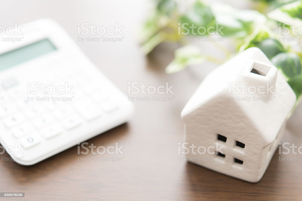 Toy house and calculator on table close-up stock photo