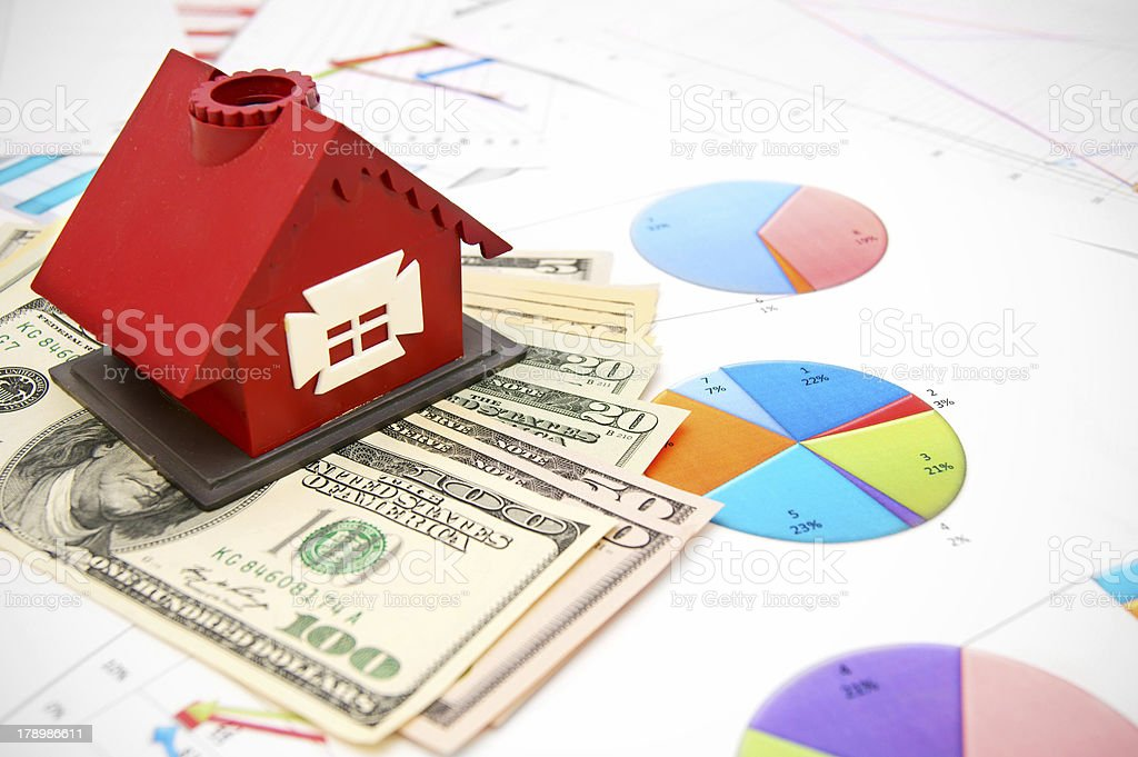 Toy house and money on the graphs. royalty-free stock photo
