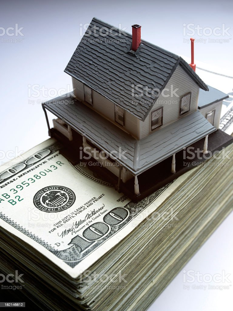 Toy house on top of stack of money stock photo