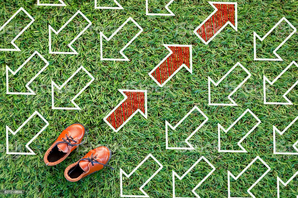 toy leather shoe on grass field and arrow direction.jpg stock photo
