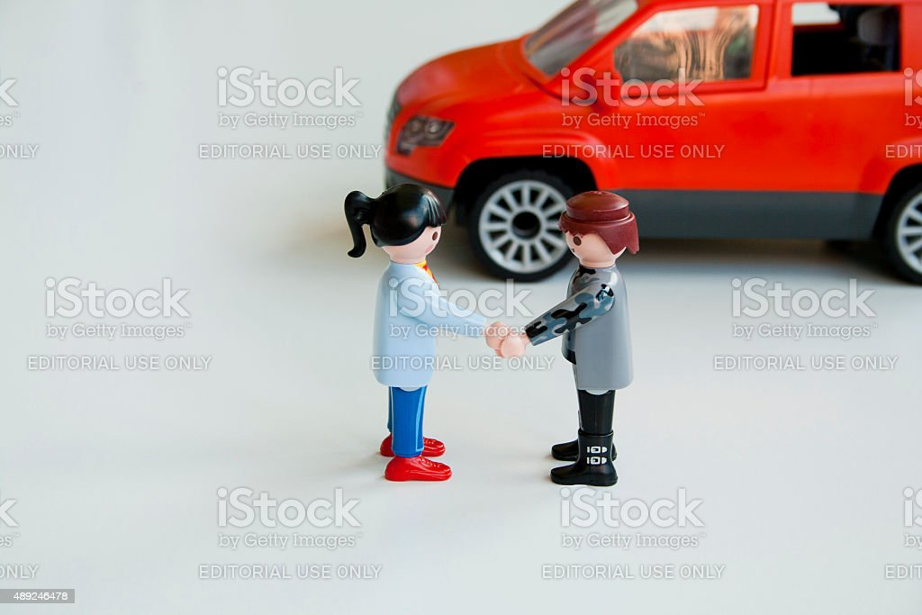 Toy man and woman shake hands to reach an agreement. stock photo