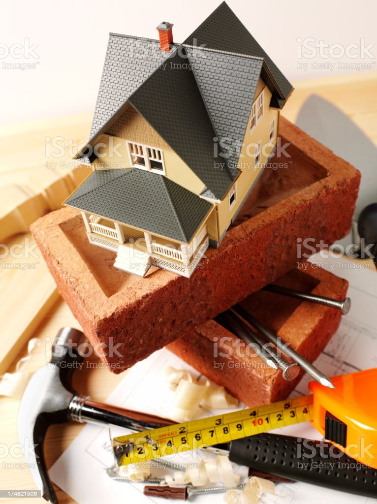 Toy Model House on Bricks with Work Tools royalty-free stock photo