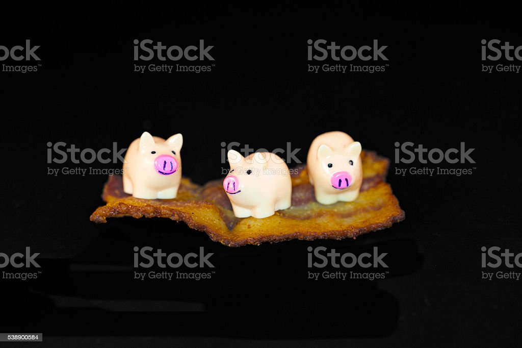 toy pigs on top of bacon stock photo