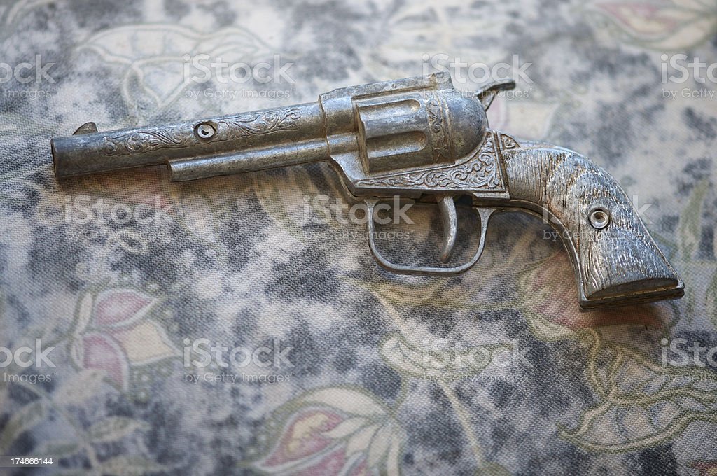 Toy Pistol Gun on Antique Background stock photo