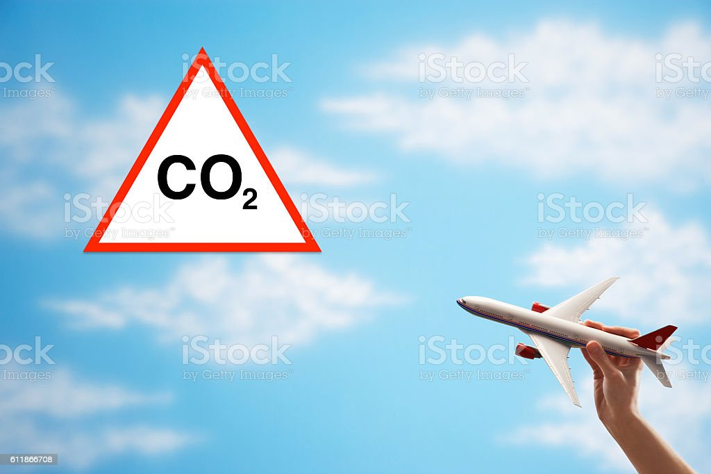 toy plane against cloudy sky with warning CO2 sign stock photo